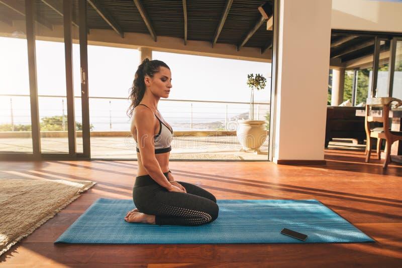 Die schöne junge Frau, die im Yoga sitzt, werfen zu Hause auf stockbild