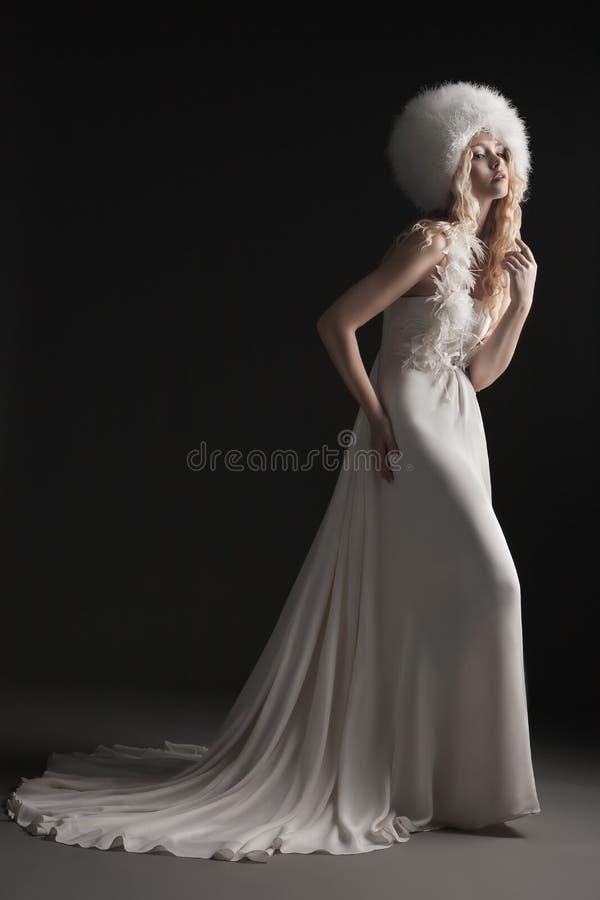 Die schöne junge Frau in einem Hochzeitskleid stockfotos