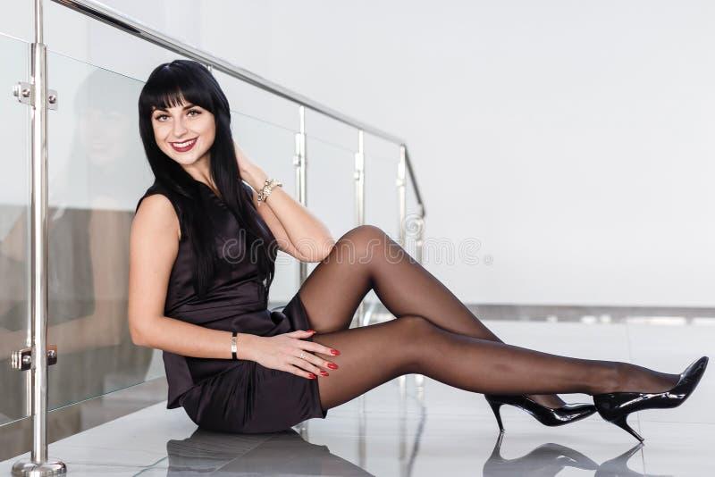 die schöne junge Frau, die in einem schwarzen Anzug mit einem kurzen Rock gekleidet wird, sitzt auf einem Boden in einem weißen B stockfoto