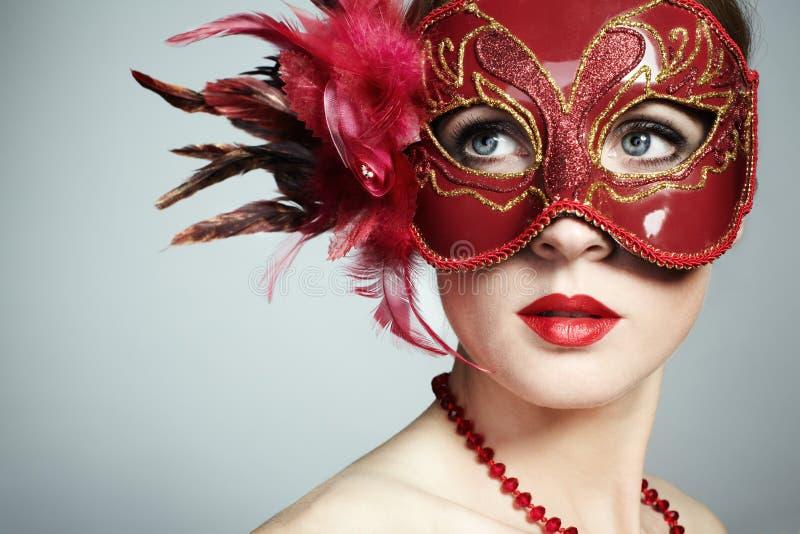 Die schöne junge Frau in einer roten venetianischen Schablone lizenzfreies stockfoto