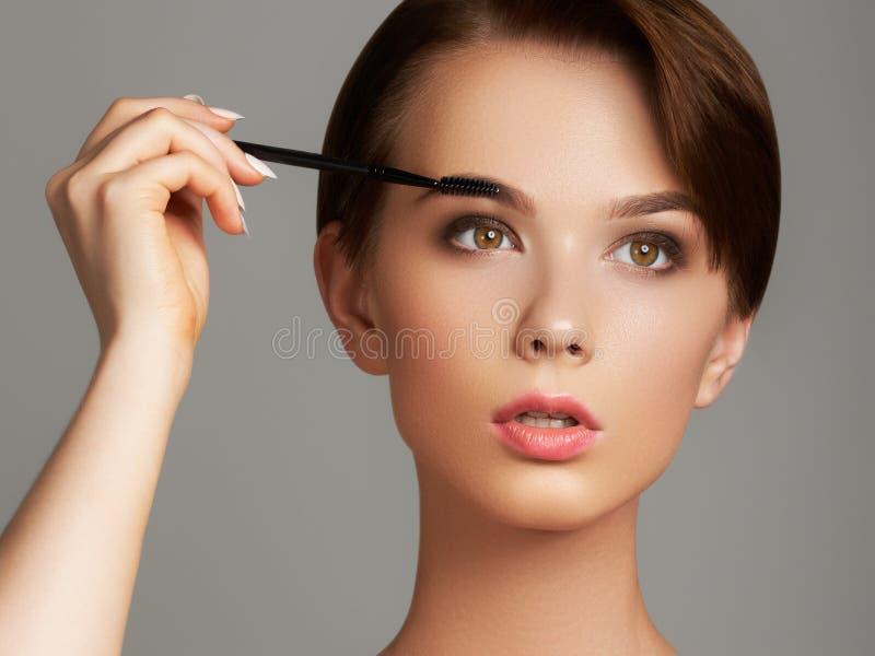 Die schöne junge Frau, die Grundlage auf ihrem Gesicht mit anwendet, bilden die Bürste, die auf grauem Hintergrund lokalisiert wi lizenzfreies stockfoto