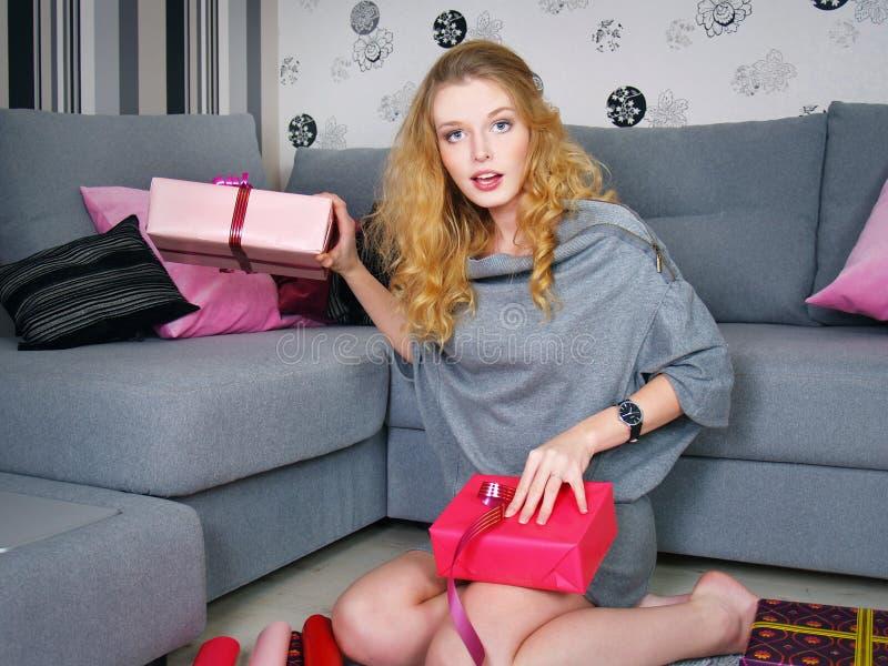 Die schöne junge Frau mit Geschenken lizenzfreie stockfotografie