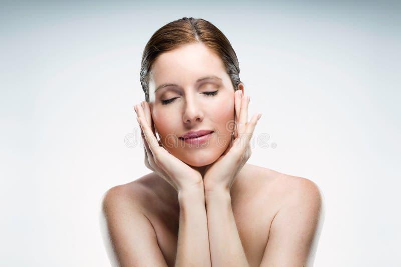 Die schöne junge Frau mit gesunder Haut und mustert die geschlossene Aufstellung lokalisiert über weißem Hintergrund lizenzfreie stockfotografie