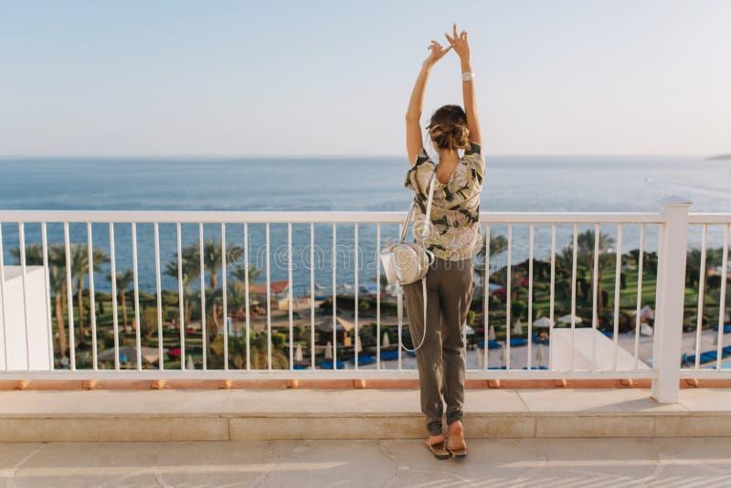 Die schöne junge Frau, die, Spaß habend sich entspannt, genießen Ansicht über Meer, Ozean auf dem Balkon, Terrasse Mädchen, Touri lizenzfreie stockfotos
