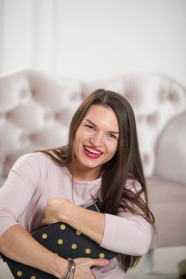 Die schöne junge Frau umfasst einen Kasten mit einem Geschenk lizenzfreies stockbild