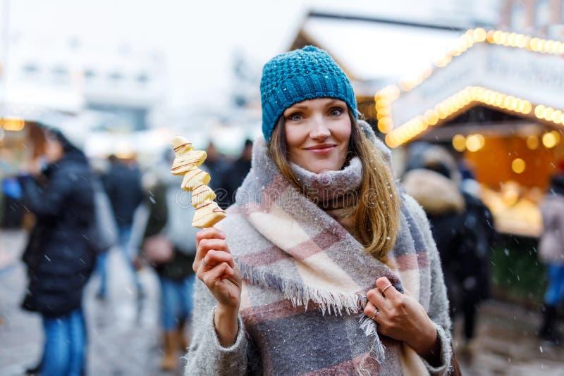 Die schöne junge Frau, die weiße Schokolade isst, bedeckte Früchte auf Aufsteckspindel auf traditionellem deutschem Weihnachtsmar lizenzfreie stockfotos