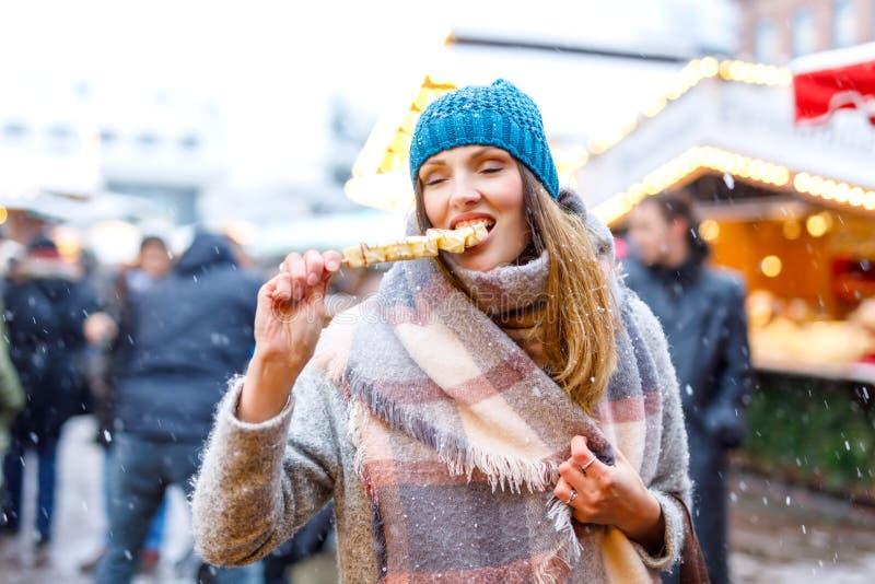 Die schöne junge Frau, die weiße Schokolade isst, bedeckte Früchte auf Aufsteckspindel auf traditionellem deutschem Weihnachtsmar lizenzfreies stockfoto