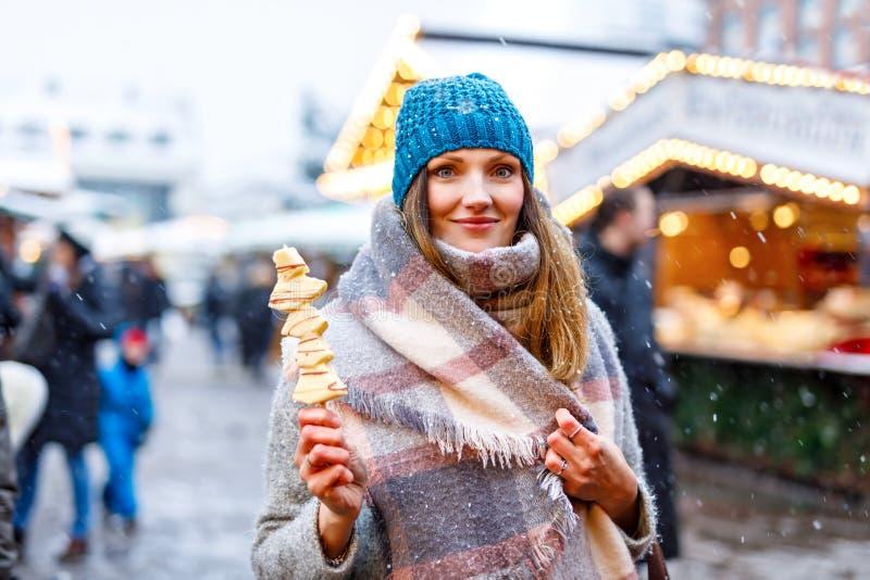 Die schöne junge Frau, die weiße Schokolade isst, bedeckte Früchte auf Aufsteckspindel auf traditionellem deutschem Weihnachtsmar stockfoto