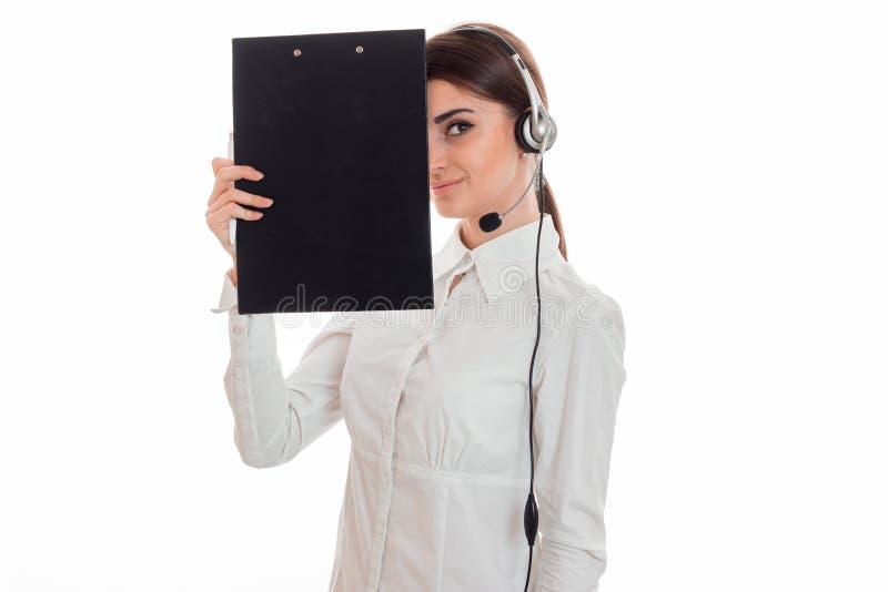 Die schöne junge Geschäftsfrau, die in Call-Center mit Kopfhörern arbeiten und das lächelnde Mikrofon und verstecken ihr Gesicht  lizenzfreie stockbilder