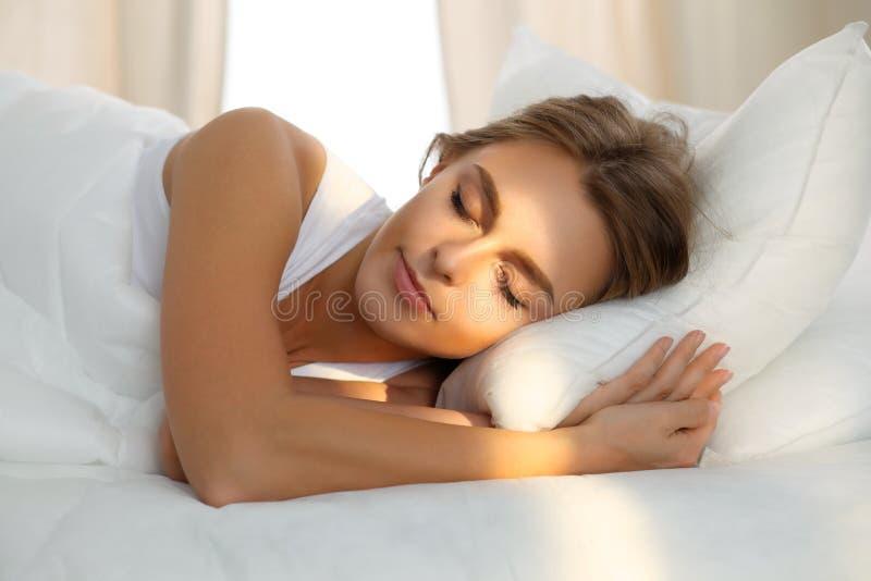 Die schöne junge schlafende Frau, beim im Bett bequem liegen und himmlisch Sonnenstrahl dämmern auf ihrem Gesicht stockbilder