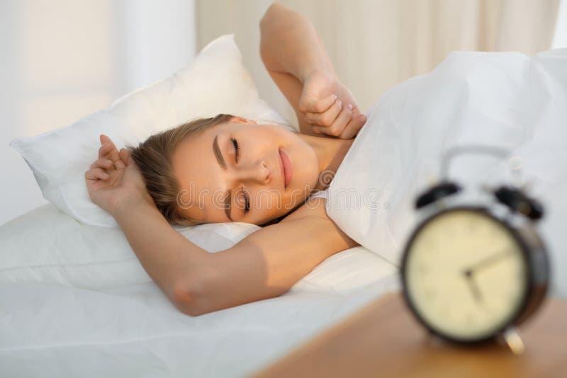 Die schöne junge schlafende Frau, beim im Bett bequem liegen und himmlisch Sonnenstrahl dämmern auf ihrem Gesicht stockbild