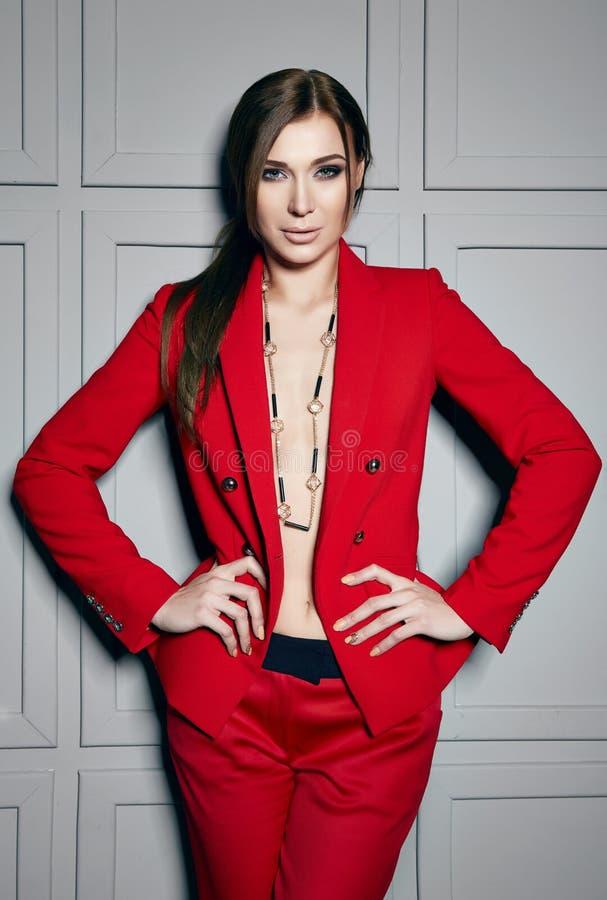 Die schöne junge sexy Brunettefrau, die stilvolles Design der roten Jacke und modernes Kostüm mit Juwel, beige Fersen trägt, besc stockbilder