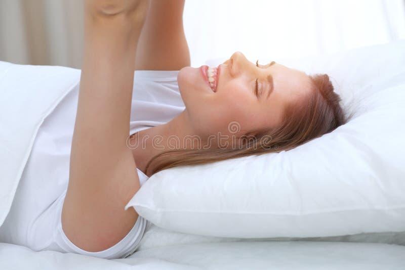 Die schöne junge und glückliche Frau, die Hände ausdehnt, beim im Bett bequem liegen und vor himmlisch lächeln wachen herein auf stockfotografie