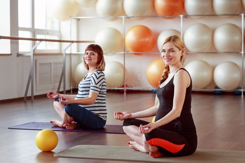 Die schöne schwangere trainierende Frau, beim Sitzen im Lotos setzen voraus lizenzfreie stockfotos