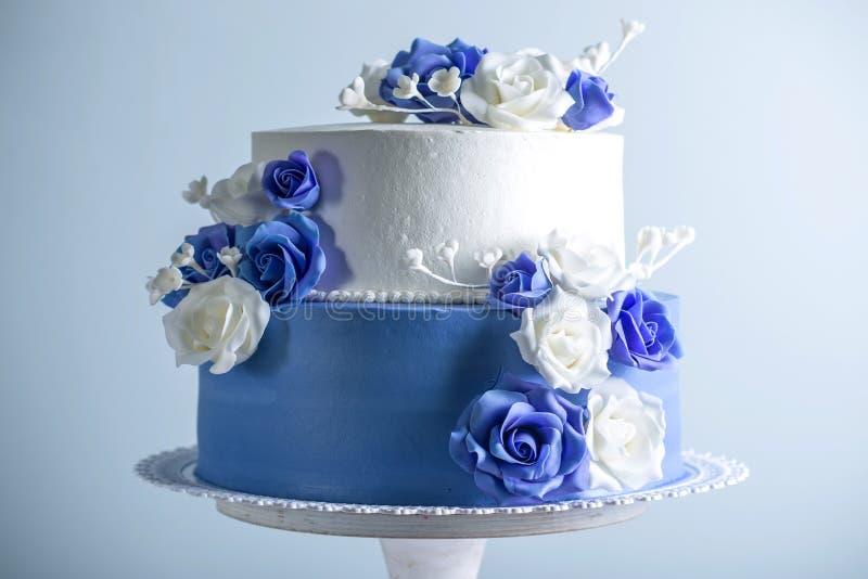 Die schöne zwei abgestufte weiße und blaue Hochzeitstorte, die mit Blumen verziert wird, zuckern Rosen Konzept von eleganten Feie stockfotografie