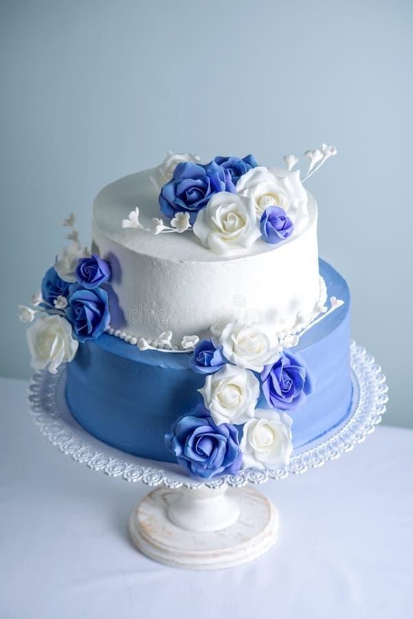 Die schöne zwei abgestufte weiße und blaue Hochzeitstorte, die mit Blumen verziert wird, zuckern Rosen Konzept von eleganten Feie lizenzfreie stockfotos