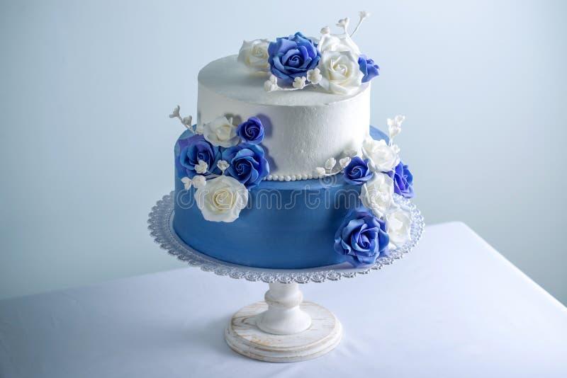 Die schöne zwei abgestufte weiße und blaue Hochzeitstorte, die mit Blumen verziert wird, zuckern Rosen Konzept von eleganten Feie stockbilder