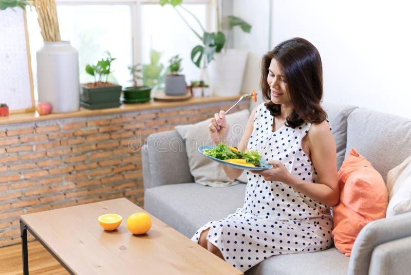 Die schönen asiatischen schwangeren Frauen, die auf Sofa sitzen, hat Salat zum ihr Frühstück, das einige Orangen auf dem Tisch ge stockbilder