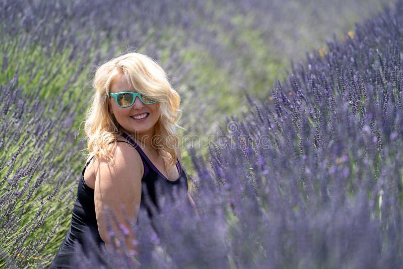 Die schönen Blondine, die Sonnenbrille tragen, sitzen auf einem Gebiet des Lavendels Eingelassener Mt Haube Oregon lizenzfreies stockfoto