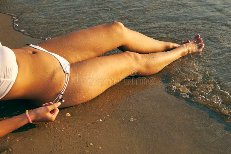 Die schönen sexy Beine der Frauen mit Wassertröpfchen auf dem Strand stockbilder