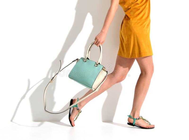 Die schönen weiblichen Beine, die Sommerschuhe in den braunen gelben Designern tragen, kleiden und blaue tadellose FrauenHandtasc stockbild