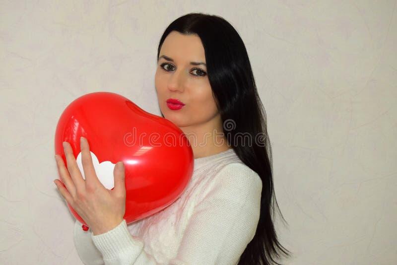 Die Schönheit der Brunette hält in der Hand den roten Ballon in Form von Herzen lizenzfreie stockfotos