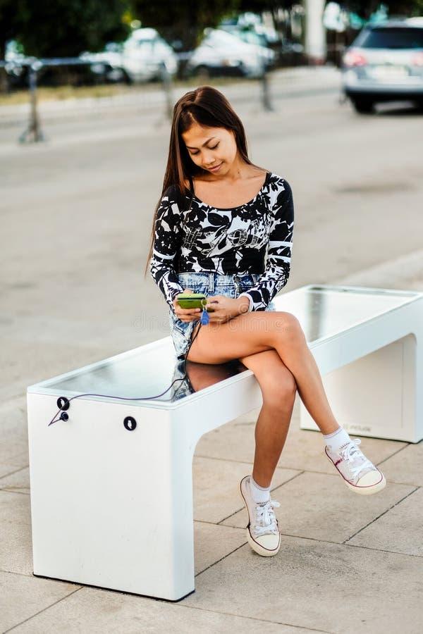 Die Schönheit, die ihr Telefon auf freiem Vielzwecksonnenkollektorladegerät auflädt, inkorporierte herein zu sitzender Bank für B lizenzfreies stockfoto