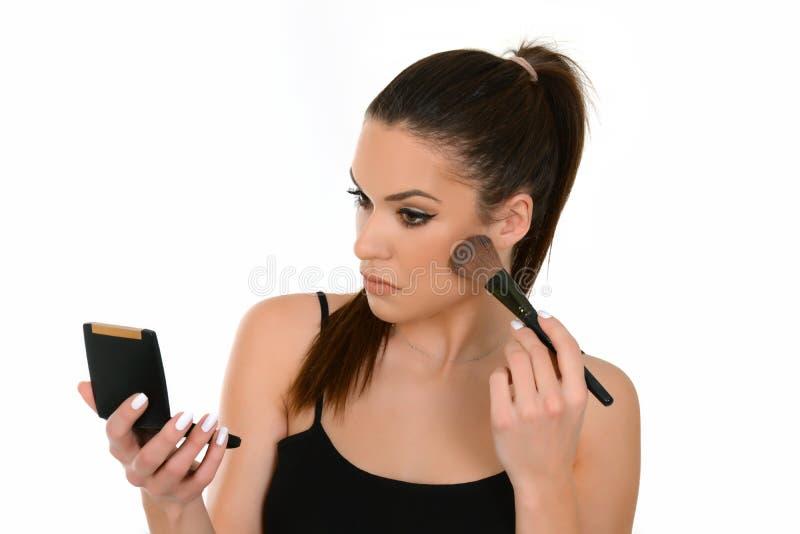 Die Schönheit, die Make-up anwendet, halten bilden Bürste und kleinen Spiegel lizenzfreie stockfotos