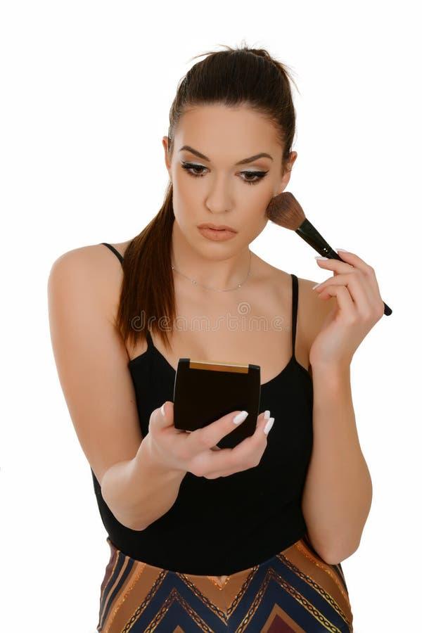 Die Schönheit, die Make-up anwendet, halten bilden Bürste und kleinen Spiegel stockfoto