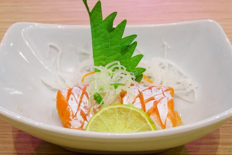 Die Schüssel des Sashimis geschmückt mit grünem shiso Blatt, geschnittener Zitrone und Weiß zerriss Rettich stockbilder