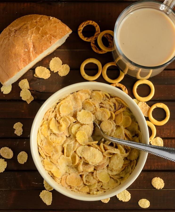 Die Schüssel von Corn-Flakes mit Glas des Kaffeegetränks und dem Stück des Weißbrots auf hölzernem Hintergrund lizenzfreies stockbild