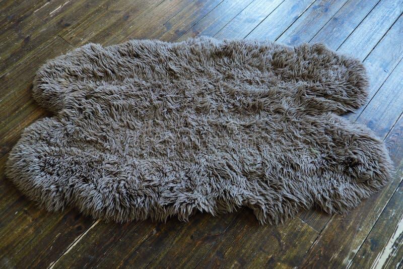 Die Schaffellwolldecke auf dem alten Bretterboden stockbild