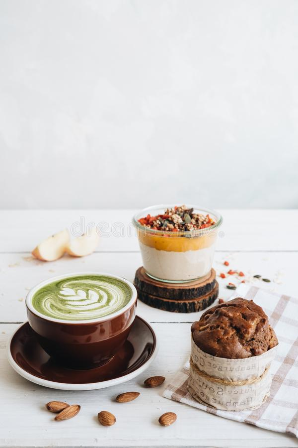 Die Schale von matcha Tee mit Mandelmilch, Mangopudding und Bananenmuffin am wei?en Tisch stockfotos