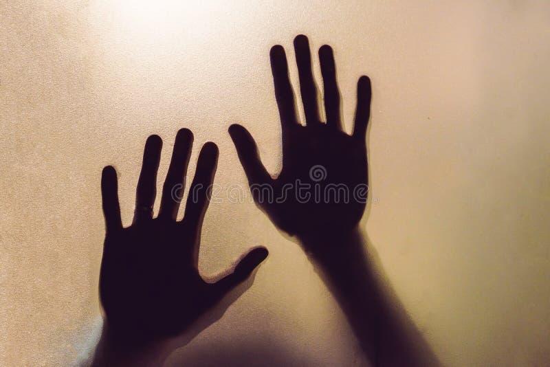Die Schattenhände des Menschen hinter dem Glas stockbilder