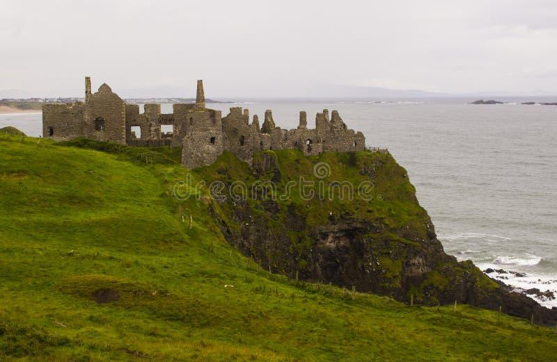 Die schattenhaften Ruinen der mittelalterlichen Iren Dunluce ziehen sich auf die Klippenoberseite zurück, die den Atlantik in Irl lizenzfreie stockfotos
