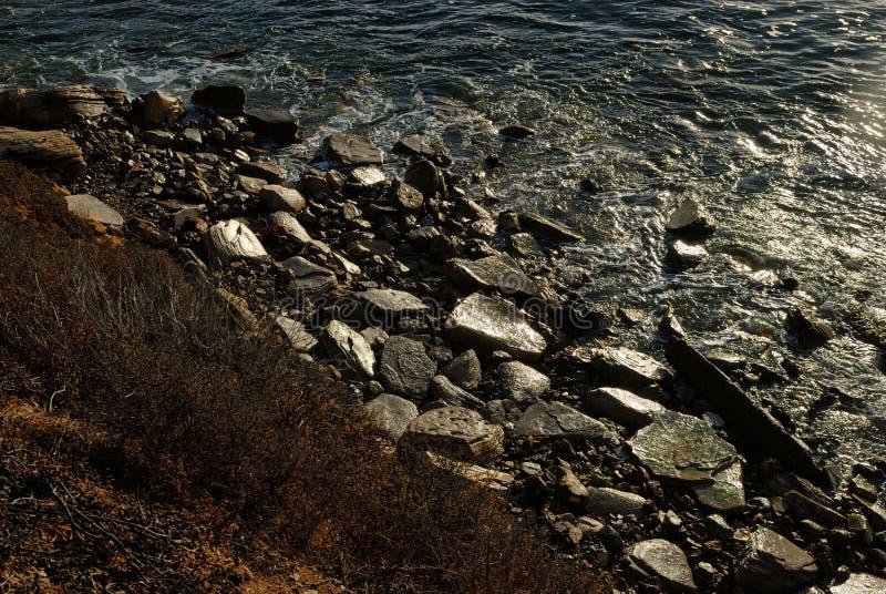 Die Schichten der Küstenlinie, wie von oben vom Wasser zu den Felsen auf dem Strand und schließlich zur trockenen Bürste auf den  stockfotos