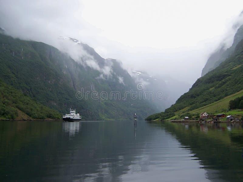 Die Schiffssegel durch die norwegischen Fjorde hinter einem kleinen Dorf auf einem nebeligen Sommermorgen stockbilder