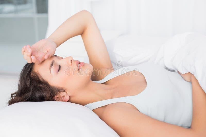 Die schläfrige junge Frau, die unter Kopfschmerzen mit Augen leidet, schloss im Bett stockfotos