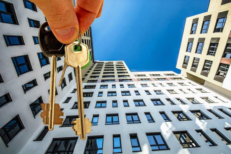 Die Schlüssel zur Wohnung im Hintergrund eines Hauses lizenzfreies stockbild