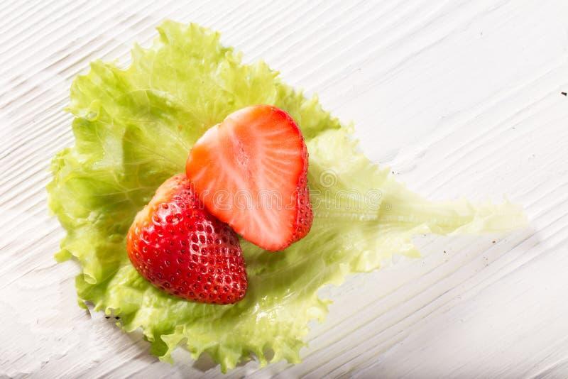Die Schnitterdbeerbeere auf einem grünen Kopfsalatblatt stockbild