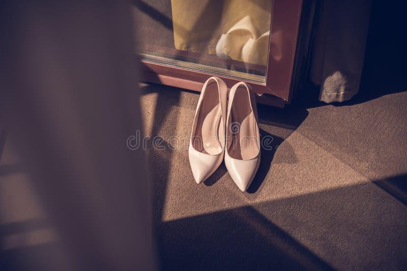 Die Schuhe der elegan ledernen Frauen der beige Stöckelschuhe auf ein hölzernes backgroundlight glatten Ferse shoesBride Schuhe lizenzfreie stockfotos