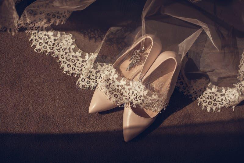 Die Schuhe der eleganten ledernen Frauen der Schuhe auf Schuhen einer Fersenschuhe Braut des hölzernen Hintergrundes hellen glat stockfoto