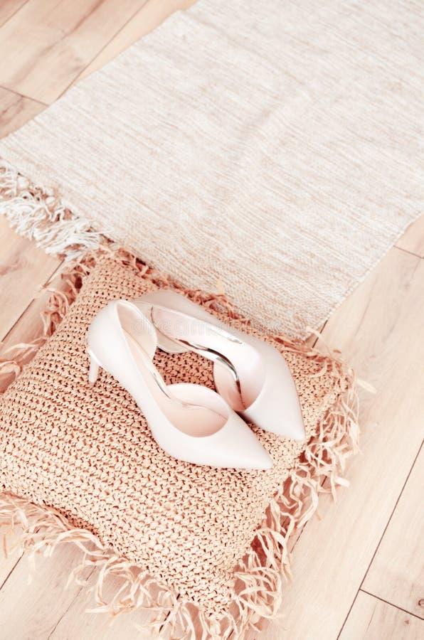 Die Schuhe der eleganten ledernen Frauen der beige St?ckelschuhe auf Schuhen einer hellen glatten Ferse des h?lzernen Hintergrund lizenzfreie stockbilder