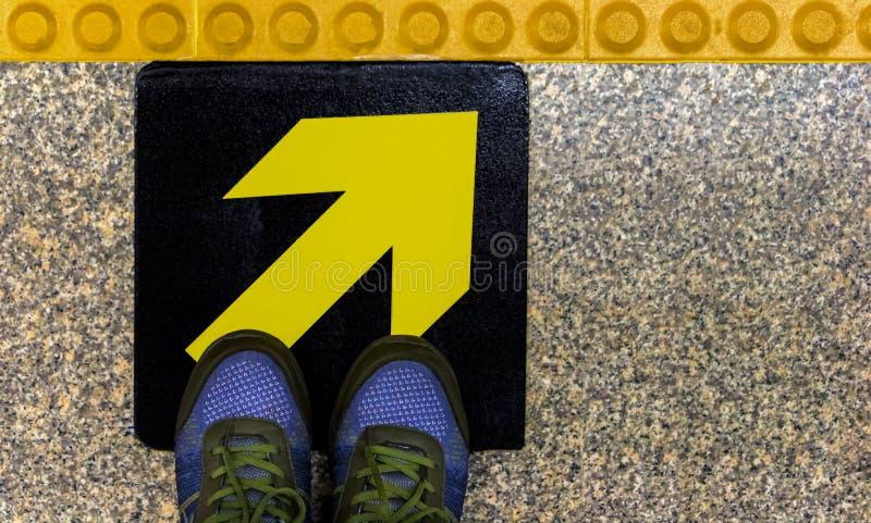 Die Schuhe der Männer auf einem gelben Wegweiser auf einem konkreten Boden Das Konzept einer Entscheidung getroffen in Übereinsti stockfotos