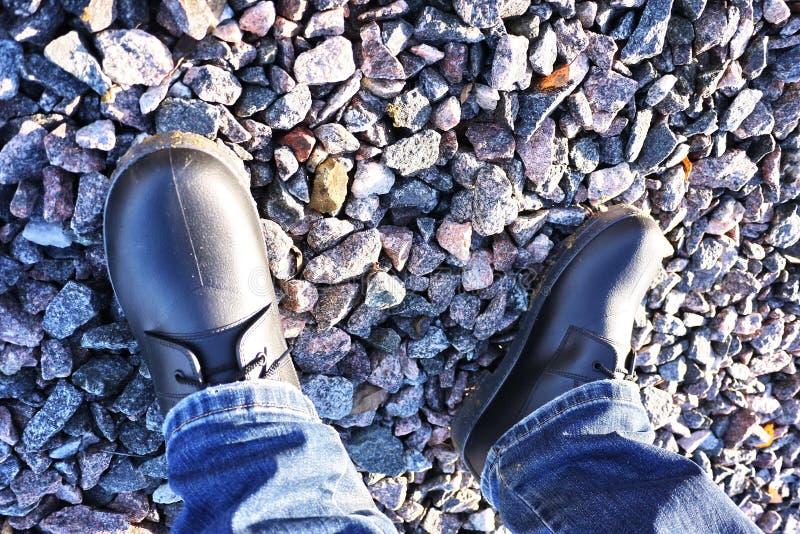 Die Schuhe der M?nner mit hoher Seite Passend w?hrend irgendeines Wetters und aller Jahreszeiten Schmutz, Schlamm, Schnee, Felsen stockfotos