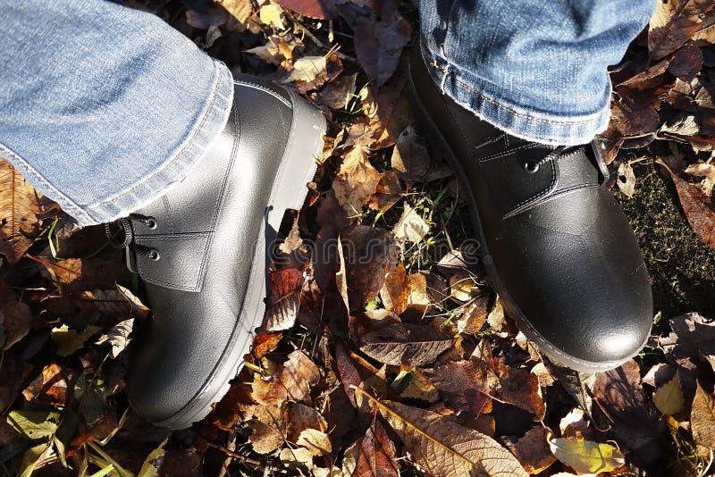 Die Schuhe der M?nner mit hoher Seite Passend w?hrend irgendeines Wetters und aller Jahreszeiten Schmutz, Schlamm, Schnee, Felsen lizenzfreie stockfotografie