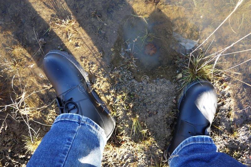 Die Schuhe der M?nner mit hoher Seite Passend w?hrend irgendeines Wetters und aller Jahreszeiten Schmutz, Schlamm, Schnee, Felsen lizenzfreie stockfotos