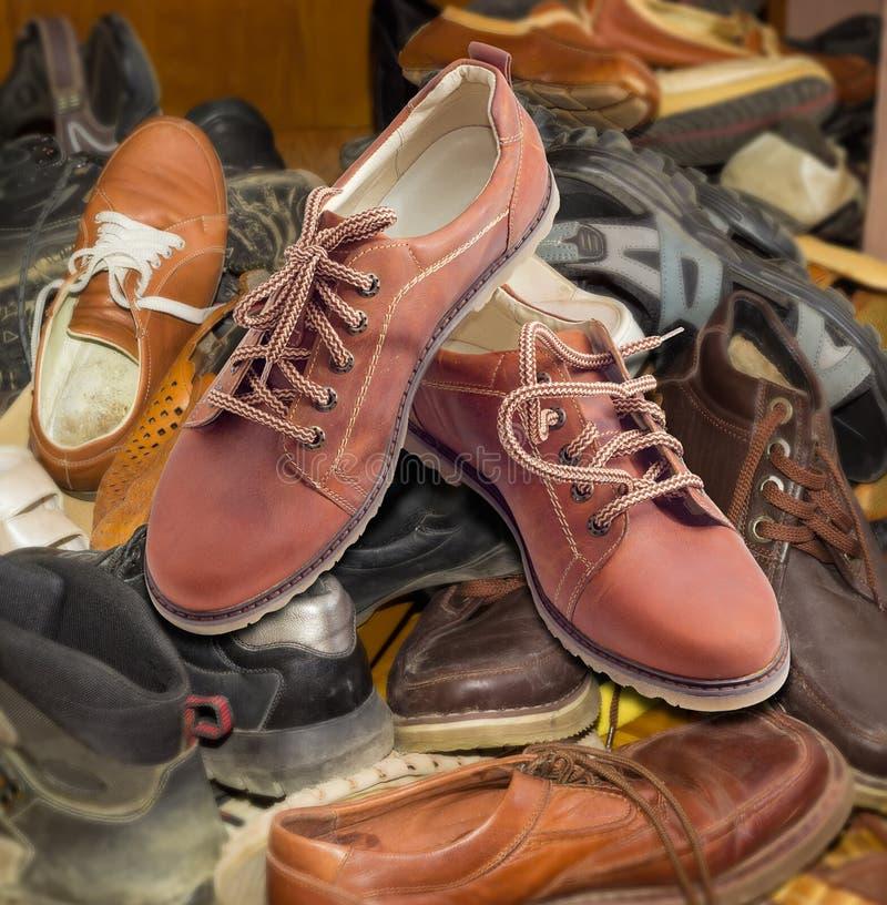 Die Schuhe der neuen Männer auf Stapel von alten unterschiedlichen getragenen Schuhen stockfotos