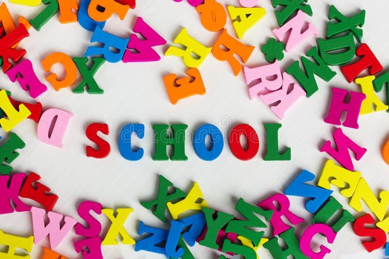 Die Schule unter den farbigen hölzernen Buchstaben lizenzfreie stockbilder