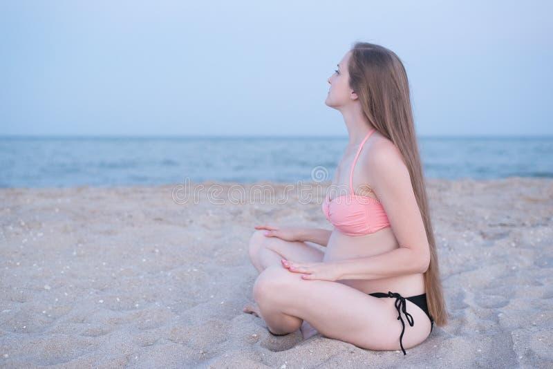 Die schwangere Frau, die auf einem Strand sitzt und meditiert Weiches Gl?ttungslicht, einsamer Strand lizenzfreies stockfoto